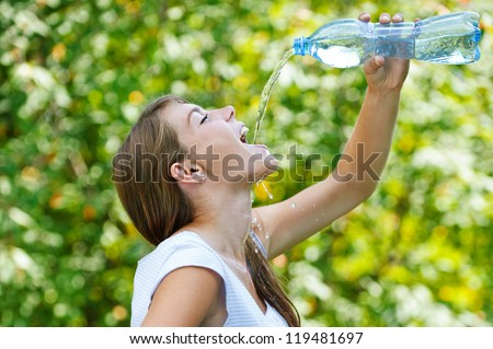 Beautiful young woman drinks water from bottle, against green of summer park. - stock photo
