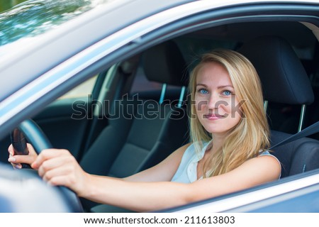 Beautiful young woman driving a car. - stock photo