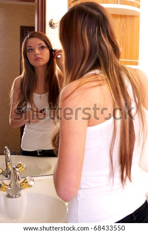 Beautiful young woman during daily morning routines - stock photo