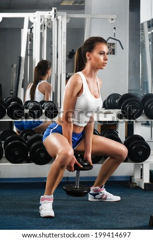 Beautiful young woman during fitness with dumbbells. - stock photo