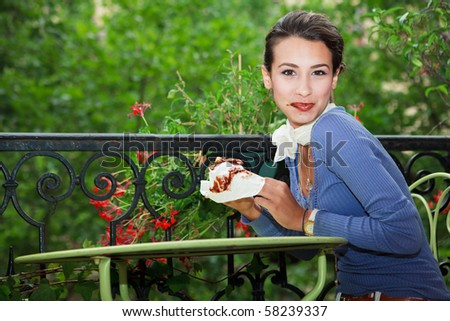 Beautiful Young Woman eating a chocolate crepe on a balcony in Paris. - stock photo