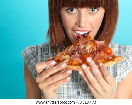 beautiful young woman, eating a slice of pizza, smiling, on blue background - stock photo