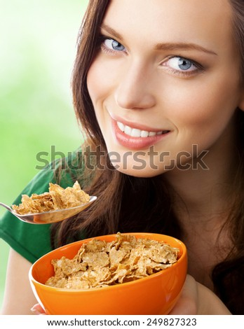 Beautiful young woman eating muesli or cornflakes, outdoor - stock photo