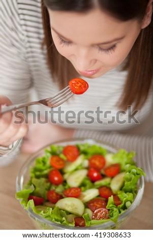 Beautiful young woman eating salad - stock photo
