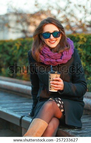 Beautiful young woman enjoying a paper cup of coffee in the summer evening downtown.  - stock photo