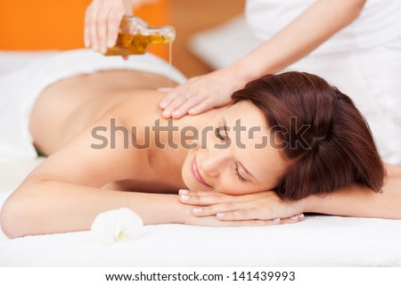 Beautiful young woman enjoying a spa beauty treatment with an oil based massage - stock photo