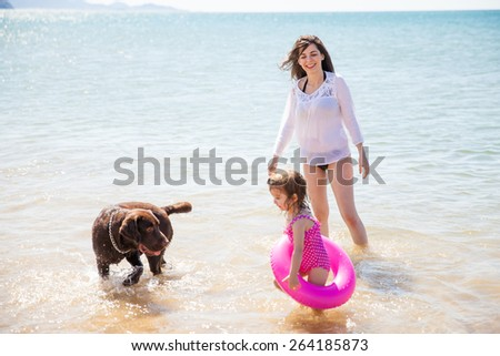 Beautiful young woman enjoying a sunny day at the beach with her daughter and her dog - stock photo