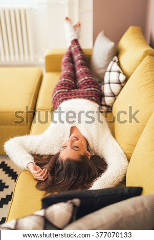 Beautiful young woman enjoying at living room. She is laying at sofa with her hands behind head. - stock photo