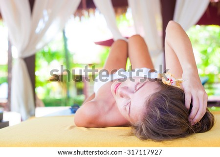 beautiful young woman enjoying her time in tropical spa - stock photo