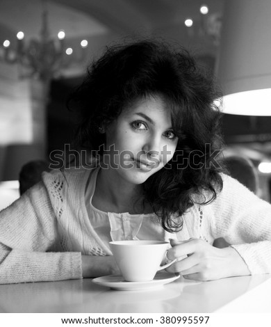 Beautiful young woman enjoying latte coffee in cafe - stock photo