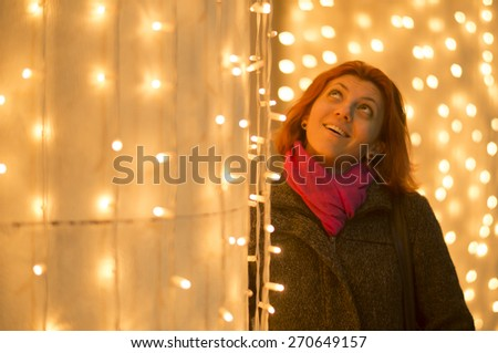 Beautiful young woman enjoying the Christmas lights decoration in the city. - stock photo