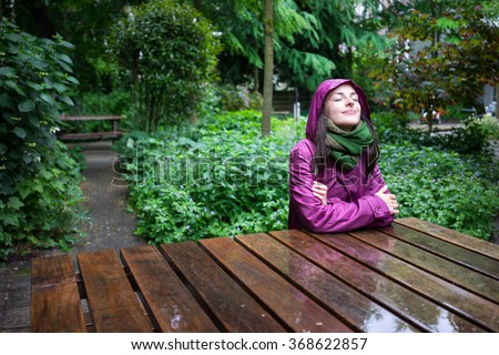 Beautiful young woman enjoying the rain in a garden decorated with eyes closed sits wooden table - stock photo