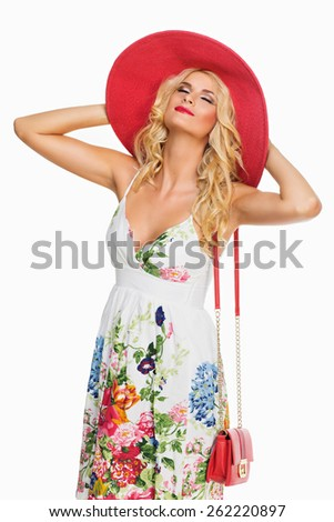 Beautiful young woman enjoying the sun wearing summerdress and large hat. Isolated ver white background - stock photo
