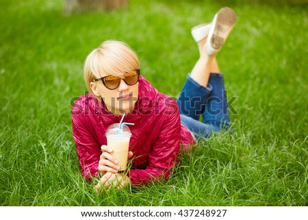 Beautiful young woman enjoys drinking coffee and lying on the grass - stock photo