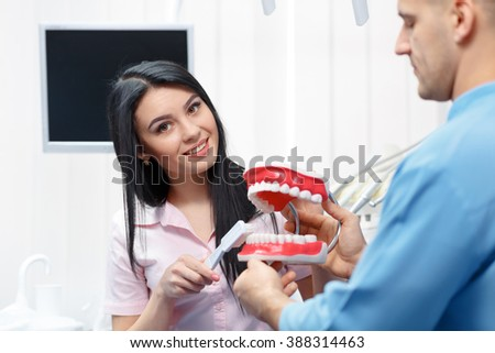 Beautiful young woman explains to dentures how to properly care for your teeth - stock photo
