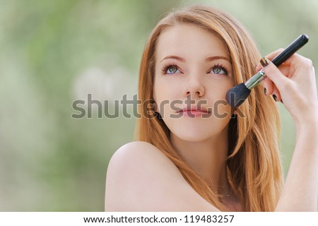 Beautiful young woman face brush handles, against background of summer green park. - stock photo