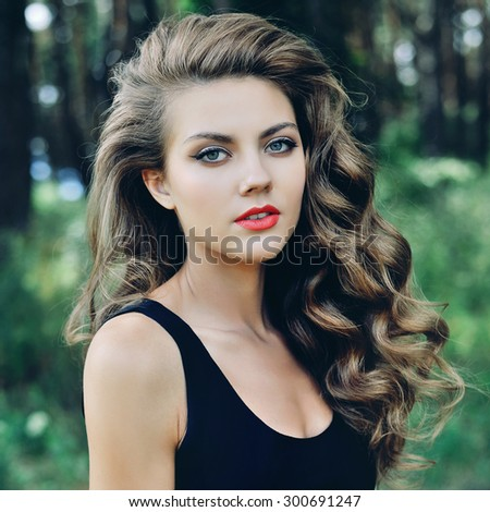 Beautiful young woman face closeup with make up and brown curly hair posing outdoor  - stock photo