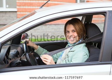 Beautiful young woman fastening in car - stock photo