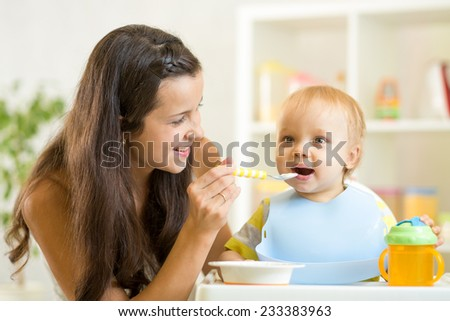 Beautiful young woman feeds son baby at home - stock photo