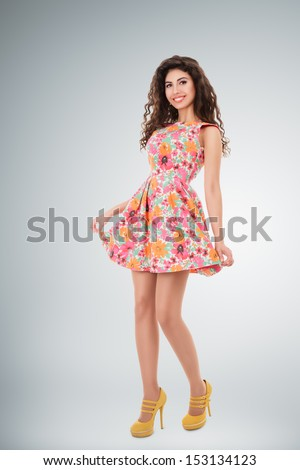 Beautiful young woman full length studio portrait over gray background - stock photo