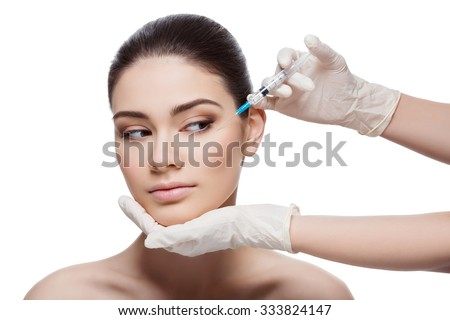 Beautiful young woman gets beauty injection in eye area from sergeant. Isolated over white background. - stock photo