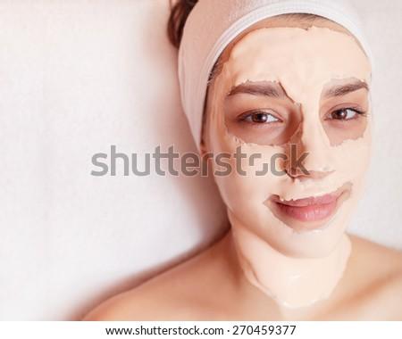 Beautiful young woman getting facial mask at beauty salon - indoors - stock photo