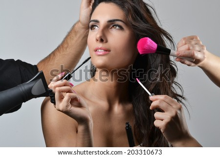 Beautiful young woman getting her hair and make up done, beauty concept, studio shot  - stock photo