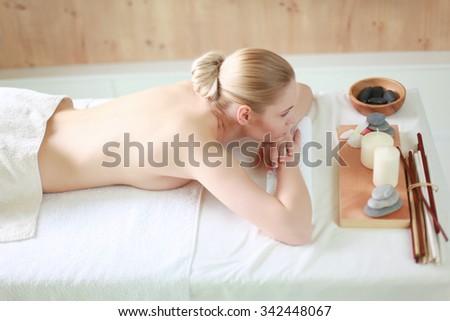 Beautiful young woman getting spa massage, lying on salon - stock photo