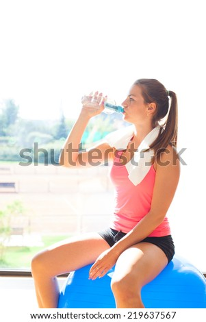 Beautiful young woman/girl after physical excercise in fitness center/gym drinking fresh water and sitting on gymnastics ball (colorful image) - stock photo