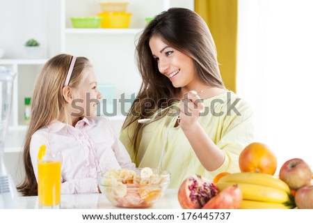 Beautiful young woman gives to the little girl a fruit salad in the kitchen. - stock photo