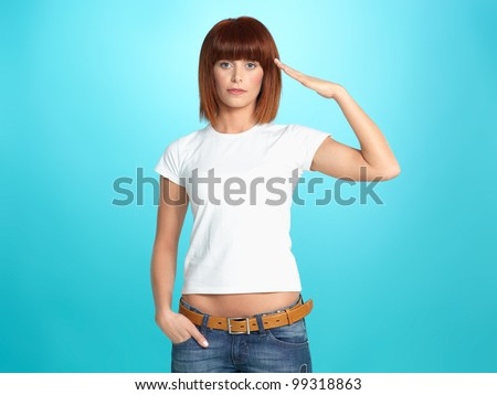 beautiful, young woman giving a military salute, on blue background - stock photo