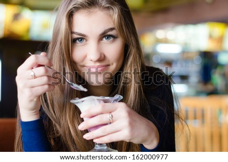 Beautiful young woman happy smiling & looking at camera sitting in restaurant or cafe and eating ice cream closeup portrait, smiling and looking in camera - stock photo