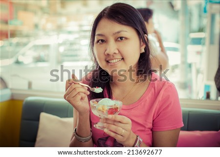 Beautiful young woman happy smiling & looking at camera sitting in restaurant or cafe and eating ice cream closeup portrait, smiling  - stock photo