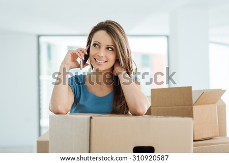 Beautiful young woman having a phone call in her new house, she is leaning on a carton box - stock photo