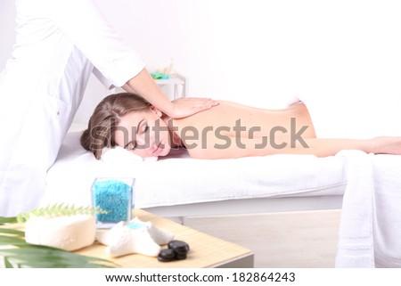 Beautiful young woman having back massage in spa salon - stock photo