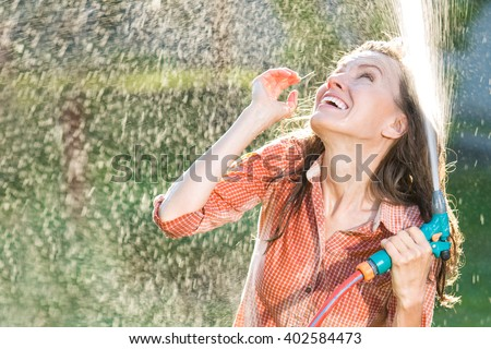 Beautiful young woman having fun in summer garden with garden hose splashing summer rain. soft backlight, motion - stock photo