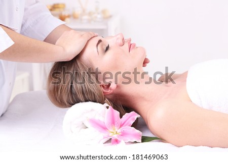 Beautiful young woman having head massage in spa salon, close-up - stock photo