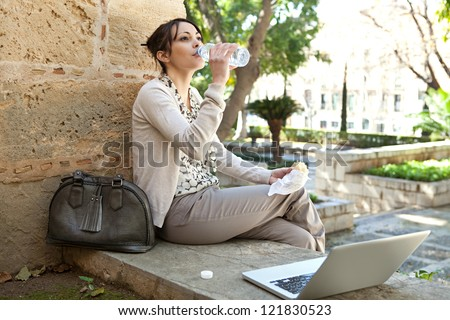 Beautiful young woman having her lunch break in a city park, using a laptop computer and drinking water from a bottle. - stock photo