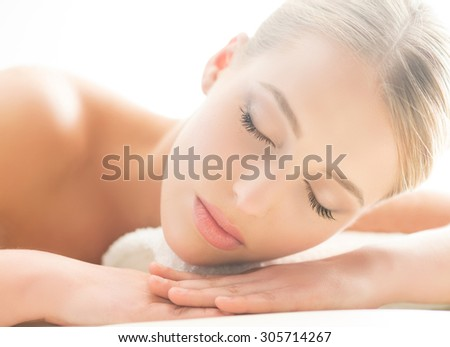 Beautiful young woman having leisure lying in a mat in spa. - stock photo