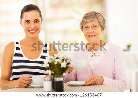 beautiful young woman having tea with grandmother or mother - stock photo