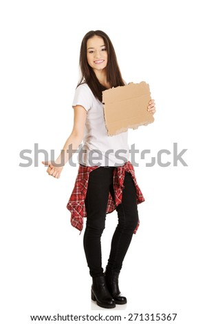 Beautiful young woman hitch hiking with empty cardboard. - stock photo