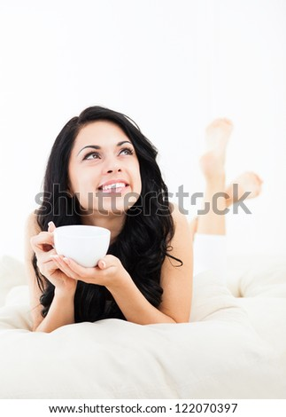 beautiful young woman hold cup of coffee lying think relaxing on the couch, sofa home indoors, happy smile day dreaming with tea mug in hands looking up away in thought - stock photo