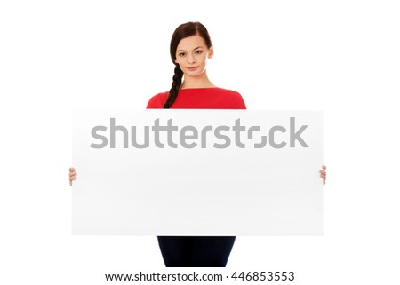 Beautiful young woman holding a blank banner - stock photo