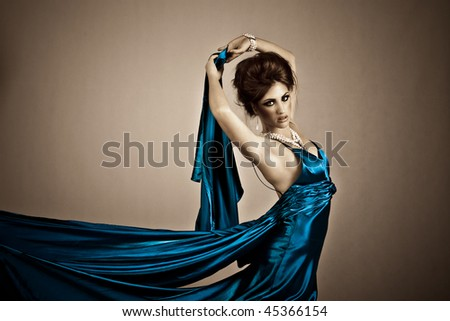 Beautiful young woman holding a blue silk dress in a fashion portrait - stock photo