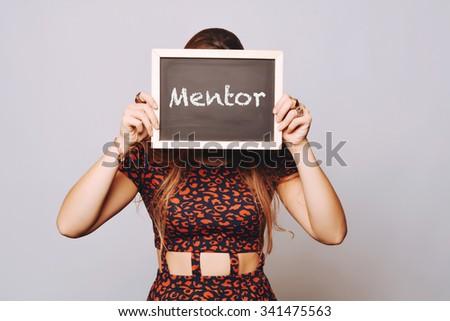 Beautiful young woman holding a chalkboard / blackboard saying mentor. Caucasian young girl. - stock photo