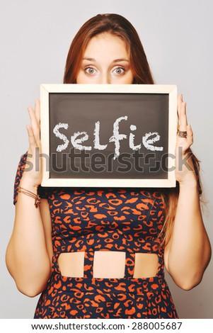 Beautiful young woman holding a chalkboard / blackboard saying selfie. Caucasian young girl. - stock photo