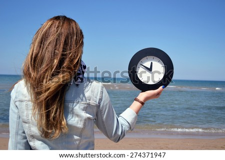 beautiful young woman holding a clock - stock photo