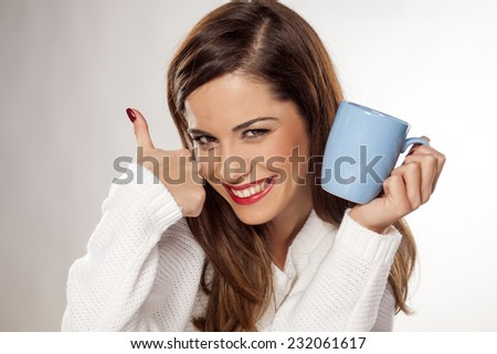 beautiful young woman holding a cup of tea and showing thumbs up - stock photo