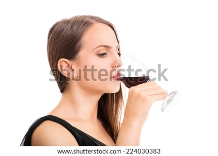 Beautiful young woman holding a glass of wine taking a sip isolated on white background - stock photo