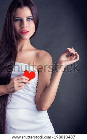 Beautiful young woman holding a heart on a dark background - stock photo
